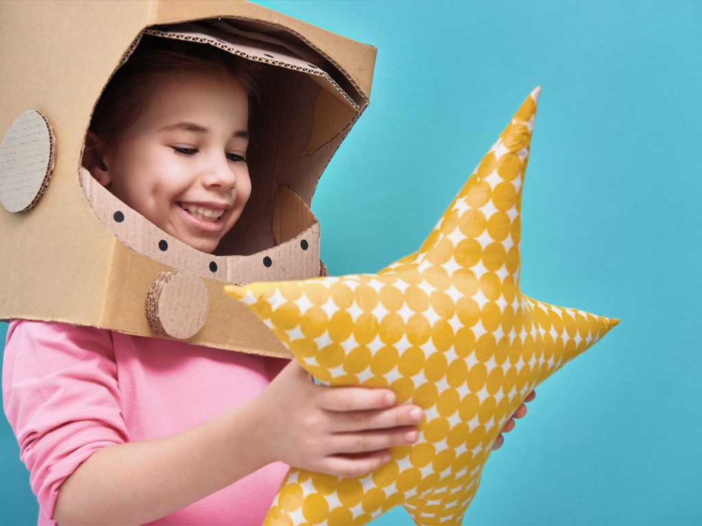 Photo of a girl playing with a star pillow
