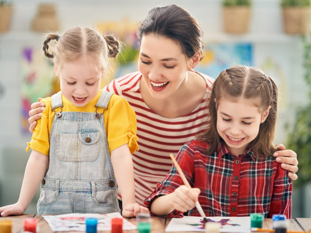 Photo of a woman painting with young children