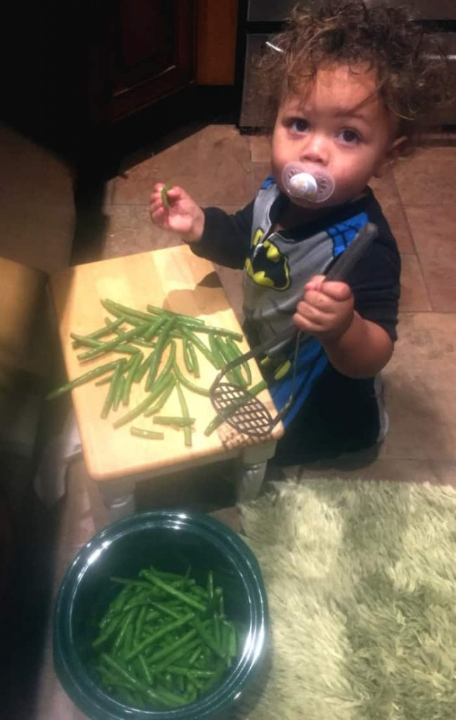 Young child cooking green beans